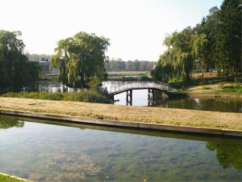 Het landschappelijk parkje met boogbrug en rotswerk, vermoedelijk aangelegd door Meyer, en de modernistische cafetaria van Van Nueten op de achtergrond; vooraan het recentelijk aangelegde ringkanaal