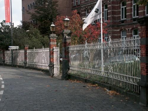 Het voortuinhek van de voormalige Provinciale School voor Vroedvrouwen aan de Guffenslaan 33, bepaalt hier de bocht van de de Hasseltse Boulevard