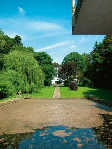 Zwembad, tegelpad en villa tegen een achtergrond van honderdjarige beuken en zilverlinden in de tuin van het kasteel van Wolsem