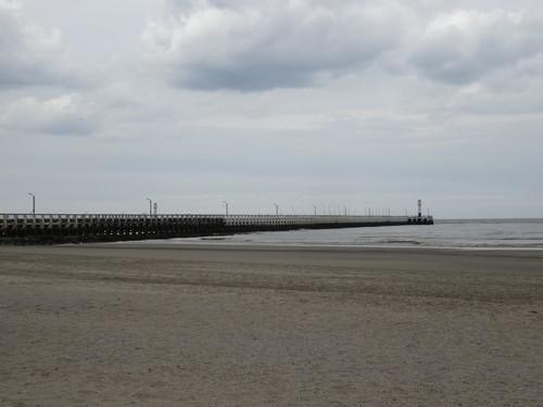 strand en havenstaketsel bij de Ijzermonding