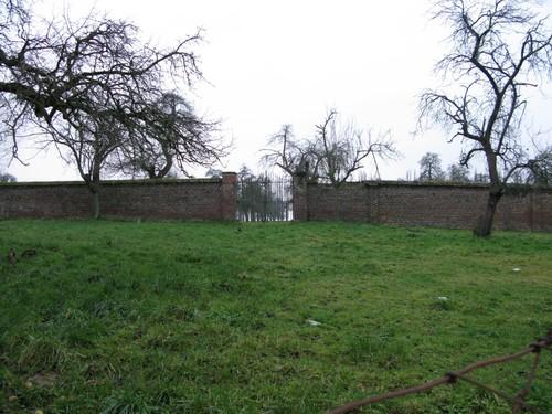 Scheidingsmuur met hek tussen beide boomgaarden